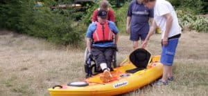 Paddle-Ability Clubs. Disabled child entering kayak.