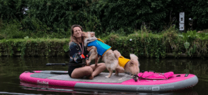 Emily paddle boarding with her dogs