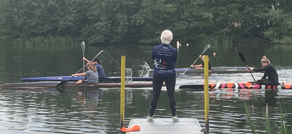 Jan, our new Performance Racing Coach, on the bank coaching four racing paddlers who are on the water.