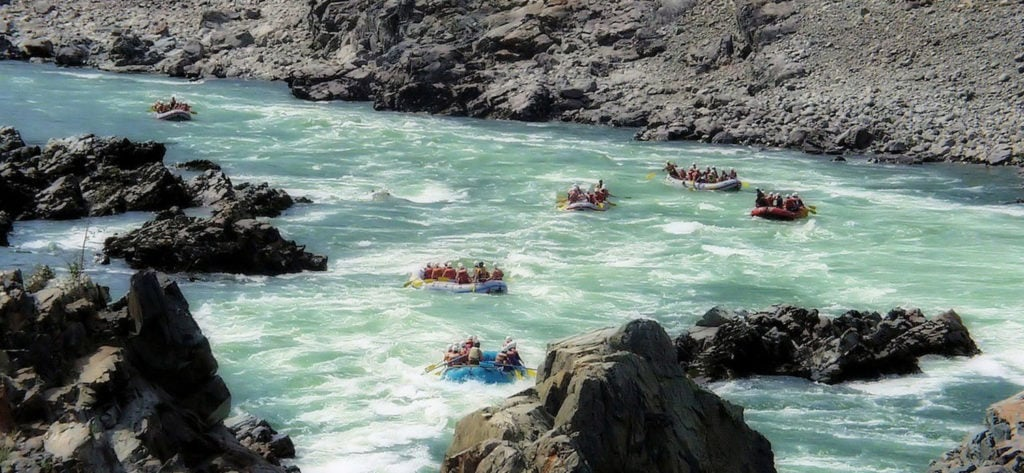 A Rafting Trip Leader negotiating the rapids with their crew