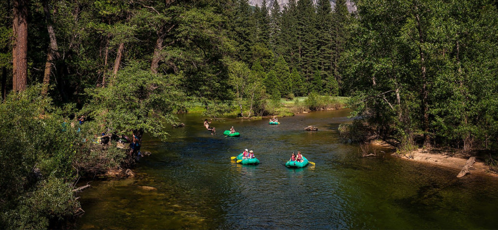 A group paddling inflatable pack rafts on a simple river trip