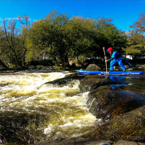 A man on a river, about to paddleboard over a mini rapid