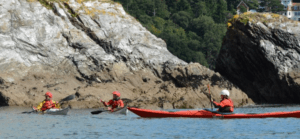 3 Sea kayakers discussing the Sea Kayak Award on the gentle sea