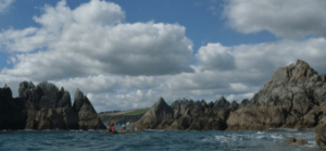 two sea kayakers paddling between some rocks on the sea