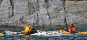 2 sea kayakers in front of some rocks, one looks on while the other practises turning