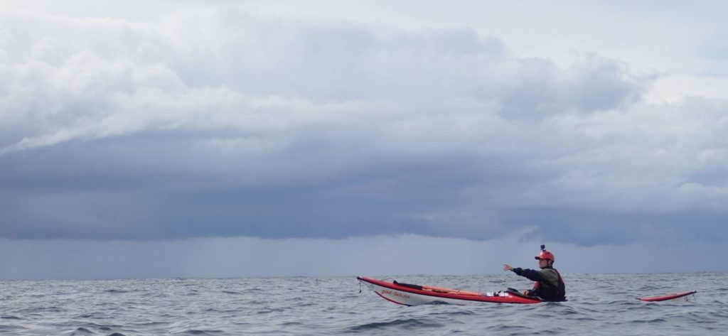 A man in a sea kayak on the sea, pointing