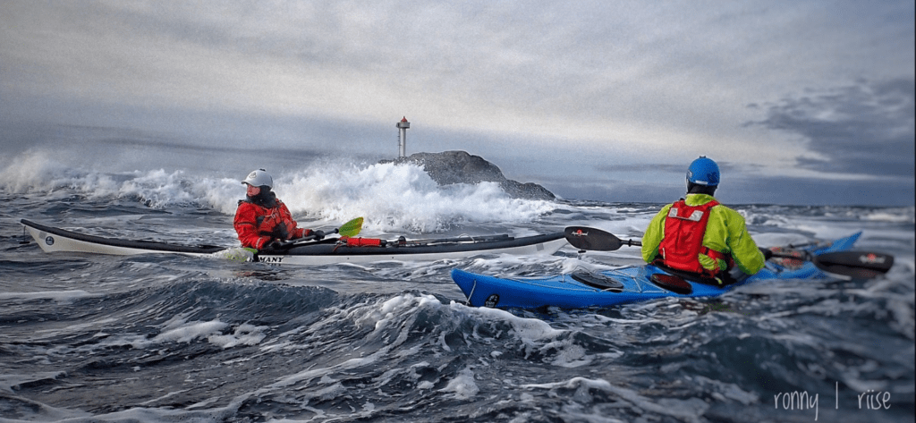 two men sea kayaking with a lighthouse in the distance