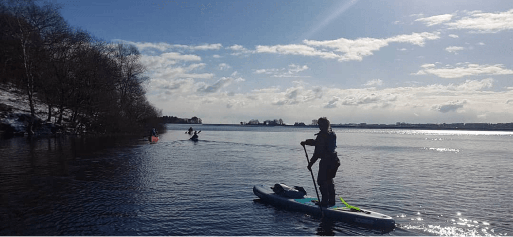 lady on a sup on a cold but sunny winters day